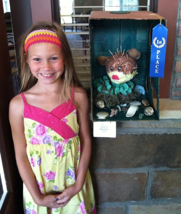 "Hannah, posing with her  award winning installation, ""Alice the Blowfish,"" Mixed Media, 2014."